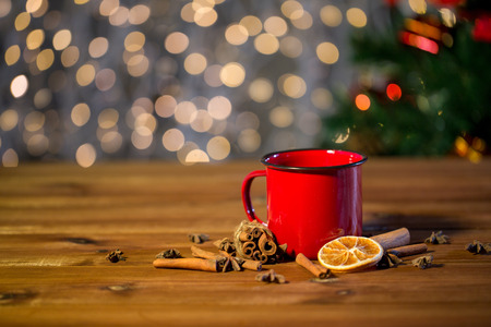 christmas tea: christmas, holidays, cooking and spice concept - close up of tea cup with cinnamon, anise and dried orange on wooden table over lights