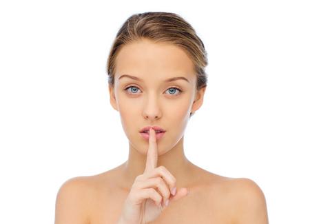 silencio: la gente, el silencio, en secreto, el gesto y el concepto de belleza - hermosa mujer joven que sostiene el dedo en los labios