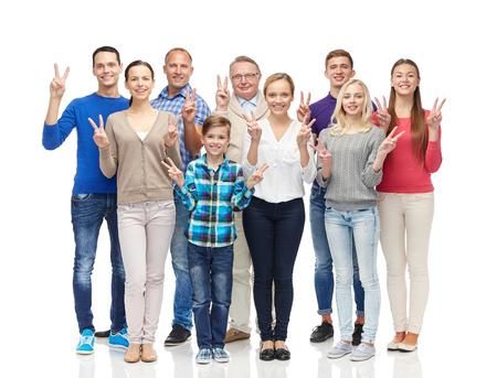 la famiglia, il sesso, la vittoria e la gente il concetto - gruppo di uomini sorridenti, donne e ragazzo che mostra il segno della mano di pace