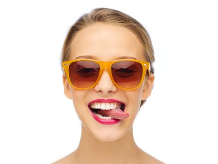 la gente, la expresión, la alegría y el concepto de la moda - mujer joven y sonriente en gafas de sol con el lápiz labial de color rosa en los labios que muestra la lengua Foto de archivo
