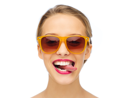 Pink lips: people, expression, joy and fashion concept - smiling young woman in sunglasses with pink lipstick on lips showing tongue