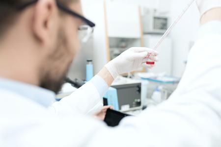 Wissenschaft, Chemie, Biologie, Medizin und Menschen Konzept - Nahaufnahme von männlichen Wissenschaftler mit Reagenzglas und Pipette Herstellung Forschung in der klinischen Labor