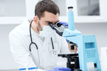 science, medicine, technology, biology and people concept - young male scientist with test tubes looking to microscope and making or research in clinical laboratory