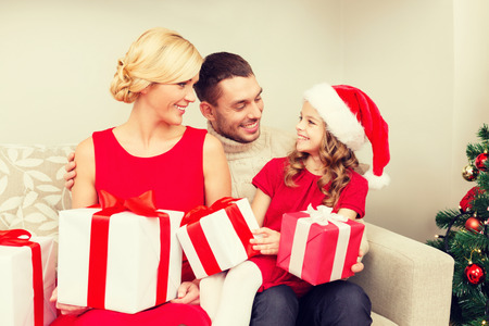 christmas tree presents: family, christmas, x-mas, winter, happiness and people concept - smiling family in santa helper hats with many gift boxes Stock Photo