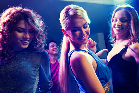 sexy party girl: party, holidays, celebration, nightlife and people concept - smiling friends dancing in club