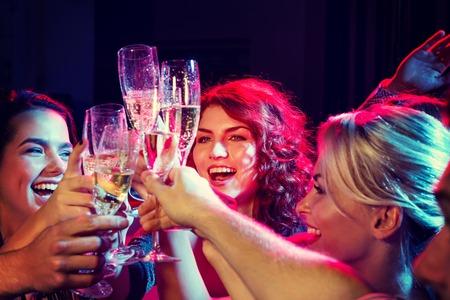 partie, vacances, célébration, la vie nocturne et les concepts - sourire amis avec des verres de champagne dans le club