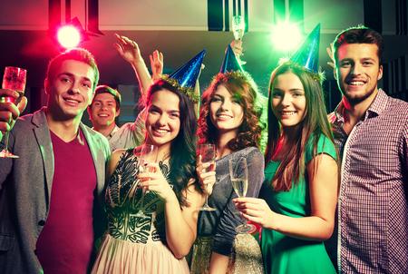 Fiesta, días de fiesta, celebración, vida nocturna y la gente concepto - amigos sonrientes en los casquillos del partido con copas de champán en el club Foto de archivo - 50589836