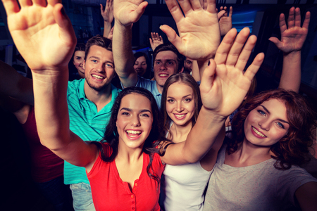 dancing club: party, holidays, celebration, friends and people concept - smiling friends dancing and waving hands in club Stock Photo
