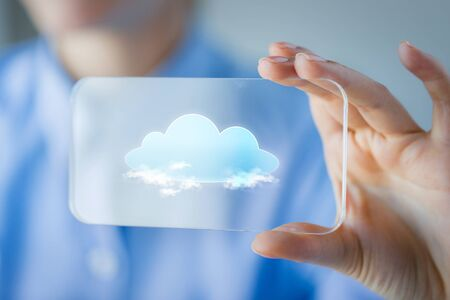 cloud technology: business, technology, computing and people concept - close up of woman hand holding and showing transparent smartphone with cloud icon on screen Stock Photo