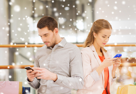 internet sale: sale, consumerism, internet addiction and people concept - young couple with shopping bags and smartphones in mall with snow effect