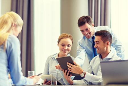 biznesu, ludzi i koncepcji technologii - uśmiechnięte działalności zespołu z komputera tablet PC spotkania w biurze Zdjęcie Seryjne