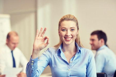 gestures: business, people and teamwork concept - smiling businesswoman showing ok gesture with group of businesspeople meeting in office