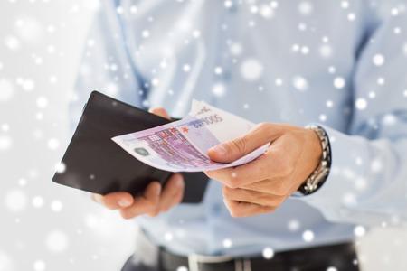 cash money: personas, negocios, finanzas y concepto del dinero - Cierre de negocios manos sosteniendo la cartera abierta con efectivo en euros sobre el efecto de la nieve