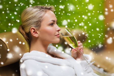 bath robe: people, beauty, lifestyle, holidays and relaxation concept - beautiful young woman in white bath robe lying on chaise-longue and drinking champagne at spa with snow effect