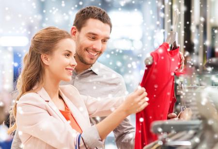 ropa de invierno: venta, el consumismo y el concepto de la gente - joven pareja feliz con bolsas de la compra eligiendo la alineada en el centro comercial con efecto de nieve Foto de archivo