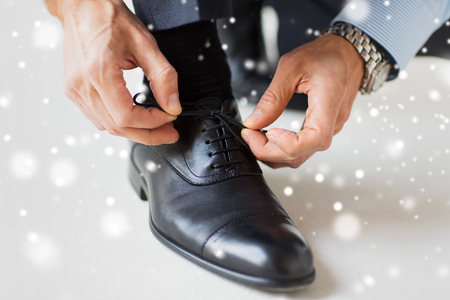 formal dressing: people, business, fashion and footwear concept - close up of man leg and hands tying shoe laces over snow effect