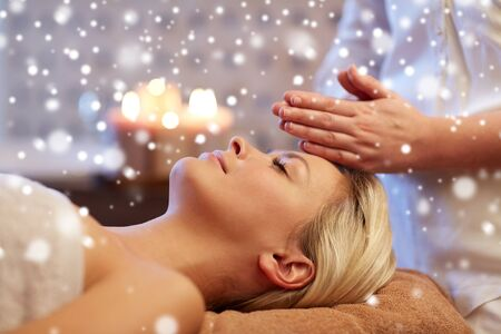 people, beauty, spa, winter and relaxation concept - close up of beautiful young woman lying with closed eyes and having face or head massage in spa with snow effect