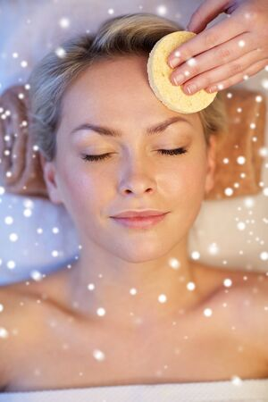 massagist: people, beauty, spa, healthy lifestyle and relaxation concept - close up of beautiful young woman lying with closed eyes and having face massage with sponge in spa with snow effect