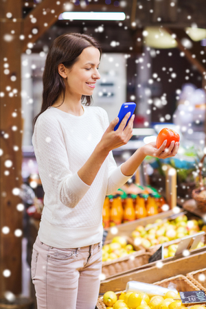 shopper: sale, shopping, consumerism and people concept - happy young woman with smartphone and tomato in market over snow effect