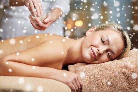 massagist: people, beauty, spa, winter and relaxation concept - close up of beautiful young woman lying with closed eyes and therapist holding salt bowl in spa with snow effect Stock Photo