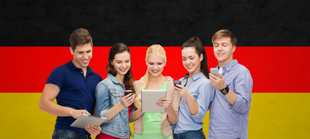 students group: people, education and modern technology concept - smiling students using smartphones and tablet pc computer over german flag background Stock Photo