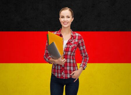 german: people, education, learning and school concept - happy and smiling teenage student girl with tablet pc and folders over german flag background Stock Photo