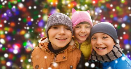 young boy smiling: childhood, leisure, friendship and people concept - group of happy kids hugging over snow background and lights Stock Photo
