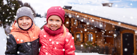 cottage: childhood, winter holidays, christmas, friendship and people concept - happy little girl and boy over wooden country house and snow background