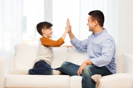 single father: family, gesture, fatherhood, generation and people concept - happy father and son doing high five at home