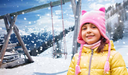 country girl: childhood, vacation, winter holidays and people concept - happy beautiful little girl portrait outdoors over swing, snow and mountains background