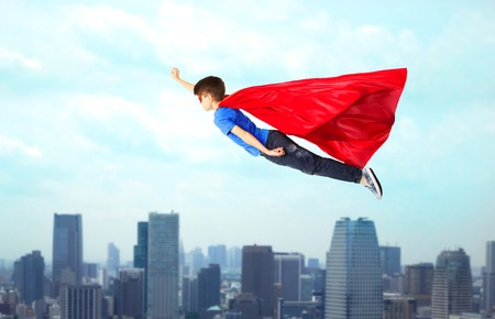 preteen boys: imagination, freedom, childhood, movement and people concept - boy in red superhero cape and mask flying in air over city background