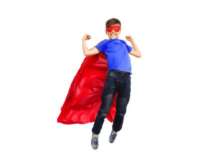 niño saltando: la felicidad, la libertad, la infancia, el movimiento y la gente concepto - muchacho en rojo capa de superhéroe y la máscara de volar en el aire