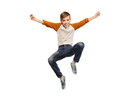 teenage boys: happiness, childhood, freedom, movement and people concept - happy smiling boy jumping in air Stock Photo