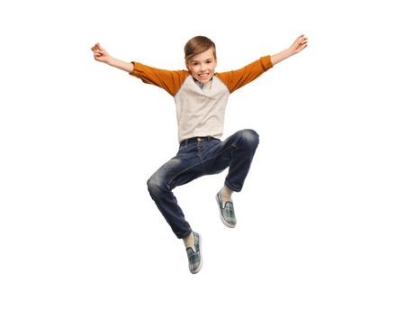 boy jumping: la felicidad, la infancia, la libertad, el movimiento y la gente concepto - muchacho sonriente feliz saltando en el aire