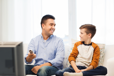 family sofa: family, people, technology, television and entertainment concept - happy father and son with remote control watching tv at home