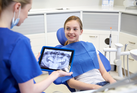people, medicine, stomatology, technology and health care concept - happy female dentist with teeth x-ray on tablet pc computer and patient girl at dental clinic office