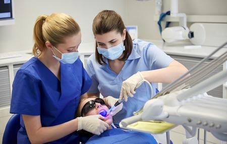 Mensen, geneeskunde, tandheelkunde en gezondheidszorg concept - vrouwelijke tandartsen met tandheelkundige genezen licht en spiegel de behandeling van de patiënt tanden meisje op tandheelkundige kliniek kantoor Stockfoto - 50748892