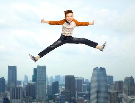 beine spreizen: Glück, Kindheit, Freiheit, Bewegung und Menschen Konzept - glücklich lächelnde Junge in der Luft über der Stadt Hintergrund Springen Lizenzfreie Bilder
