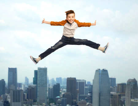 legs spread: happiness, childhood, freedom, movement and people concept - happy smiling boy jumping in air over city background