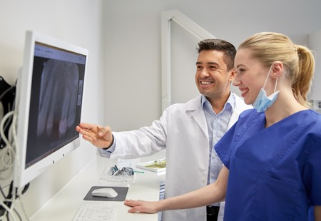 dental: people, medicine, stomatology, technology and health care concept - happy dentists looking to x-ray scan on monitor at dental clinic Stock Photo