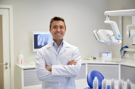 dentist concept: people, medicine, stomatology and healthcare concept - happy middle aged male dentist in white coat at dental clinic office Stock Photo