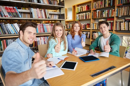 university application: people, knowledge, education and school concept - group of happy students with tablet pc computers showing thumbs up in library Stock Photo