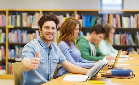 ludzie, wiedza, edukacja i koncepcji szkoły - szczęśliwy student chłopiec z książek przygotowanie do egzaminu w bibliotece i pokazując kciuk do góry gestem