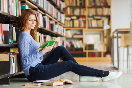 book reading: people, knowledge, education and school concept - happy student girl sitting on floor and reading book in library Stock Photo