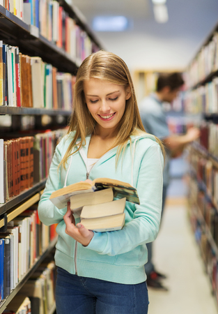 student in library: people, knowledge, education and school concept - happy student girl or young woman with book in library
