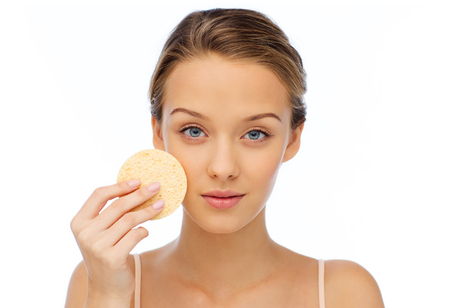 washing face: beauty, people and skincare concept - young woman cleaning face with exfoliating sponge Stock Photo
