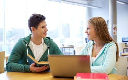dos personas conversando: las personas, la educación, la tecnología y el concepto de la escuela - estudiantes felices con el ordenador portátil y los libros en la biblioteca Foto de archivo