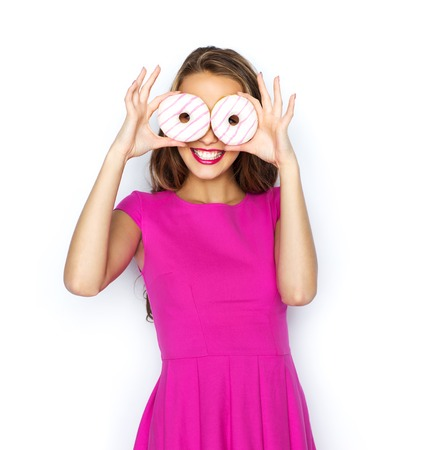 donut style: people, holidays, junk food and fast food concept - happy young woman or teen girl in pink dress having fun and looking through donuts Stock Photo