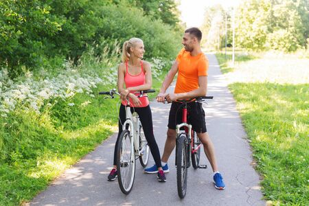 cycler: fitness, sport, people and healthy lifestyle concept - happy couple riding bicycle outdoors at summer
