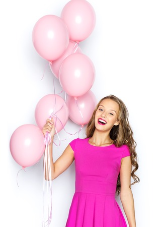 happy teens: beauty, people, style, holidays and fashion concept - happy young woman or teen girl in pink dress with helium air balloons